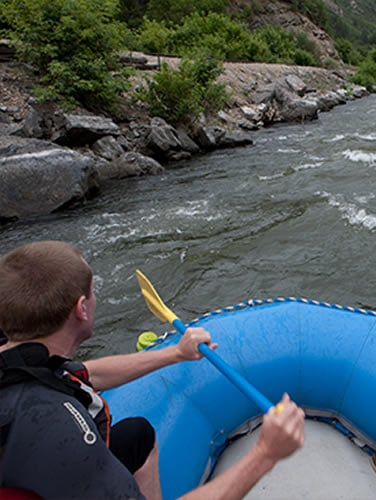 Man rafting on a rapid river
