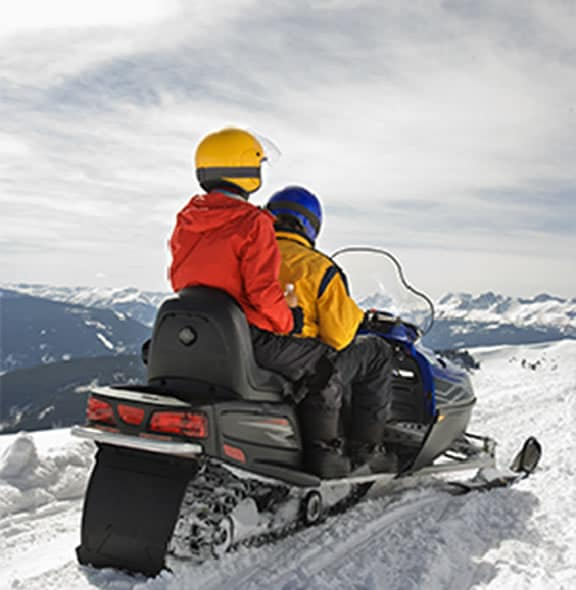 Enojying the view of a snowy mountain from a snowmobile