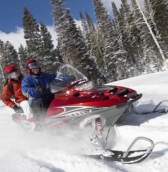Rider and Passenger on snowmobile in the mountains