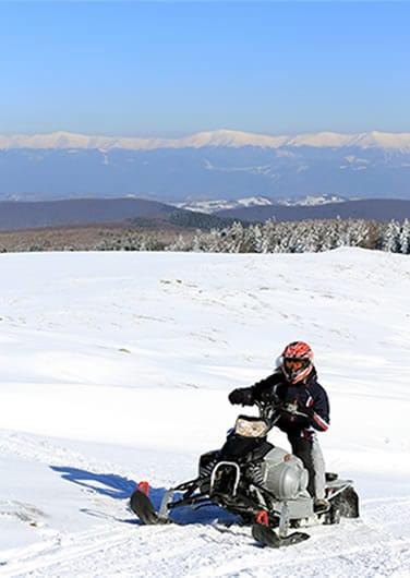 Riding a snowmobile across an empty plain
